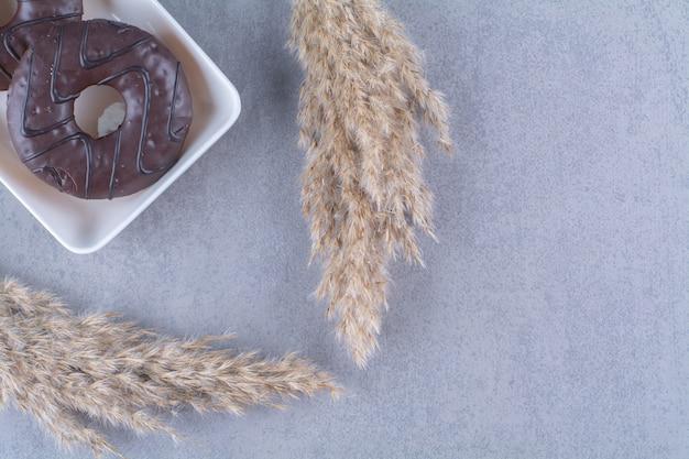 Zoete heerlijke chocoladedoughnuts op witte platen.