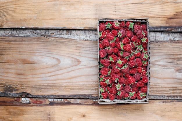 Zoete heerlijke frambozen in doos op rustieke, bovenaanzicht