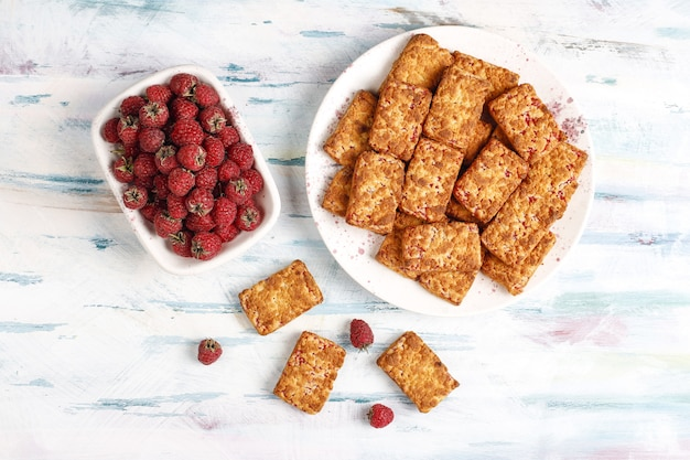 Zoete heerlijke frambozenjamkoekjes met rijpe frambozen, bovenaanzicht