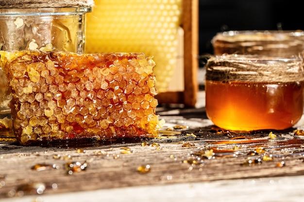 Zoete honing in de kam, glazen pot met honing op houten achtergrond
