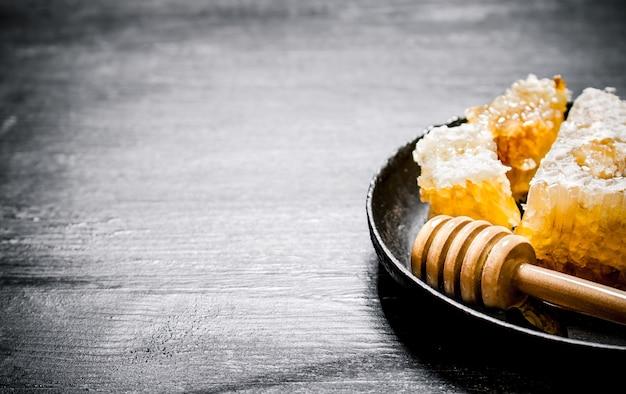 Zoete honing in de kam met een lepel in de pan