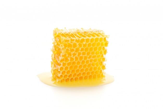 Zoete honingraat die op wit wordt geïsoleerd