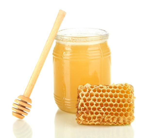 Zoete honingraat en bank met honing die op wit wordt geïsoleerd