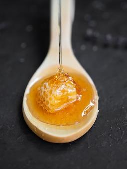 Zoete honingraat op houten lepel
