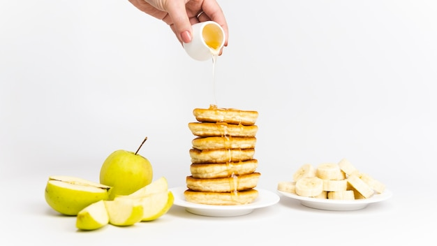 Zoete huisgemaakte pannenkoeken met banaan, appel en honing of ahornsiroop