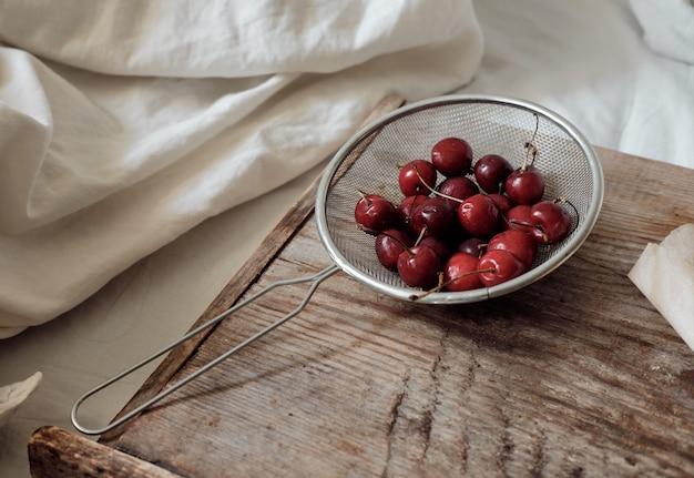Zoete kers in een metalen zeef. dessert met rode bessen. bessen op een houten dienblad.