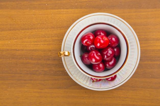 Zoete kersen in een witte kop op een houten tafel met twee kersen