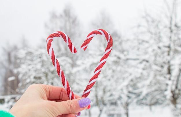 Zoete kerstkaramelstokken van rode kleur in de hand van het meisje op een besneeuwd park