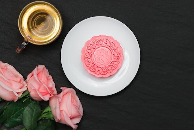 Zoete kleur van sneeuwhuid mooncake en theekop met bloemen.
