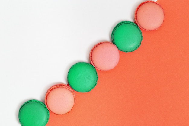 Zoete kleurrijke bitterkoekjes in rij. de heldere makaronkoekjes sluiten omhoog op document achtergrond. bovenaanzicht.