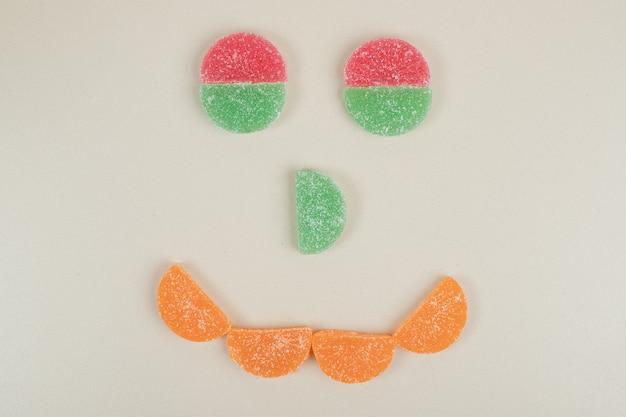 Zoete kleurrijke geleisuikergoed gevormd als gezicht
