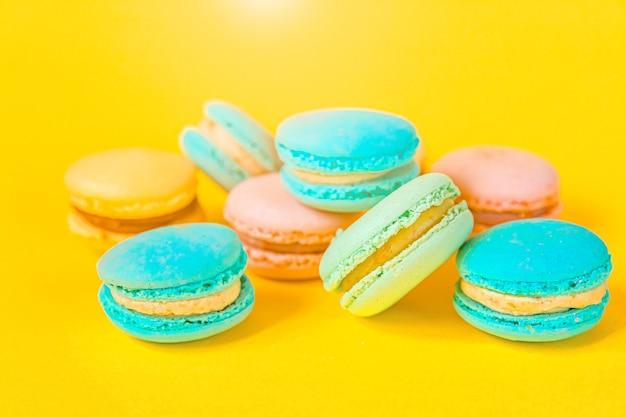 Zoete kleurrijke macarondessertcake die op trendy geel wordt geïsoleerd