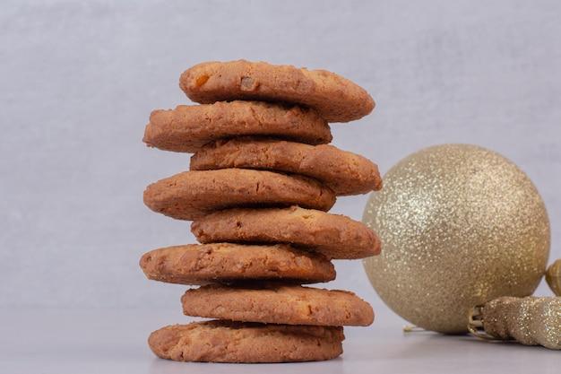 Zoete koekjes met gouden kerstballen op witte tafel.