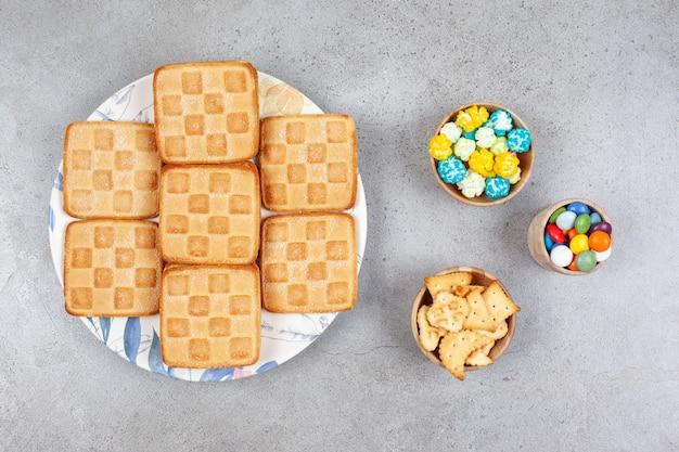 Zoete koekjes met kleurrijke snoepjes op een grijze ondergrond