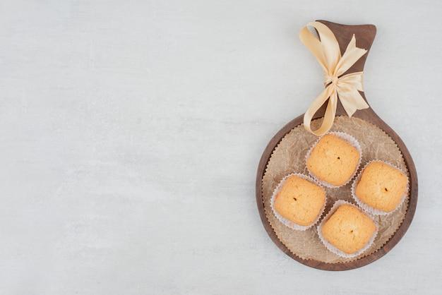 Zoete koekjes met room op houten plaat die met lint wordt verfraaid.