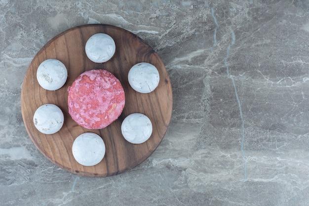 Zoete koekjes op een houten bord over grijs.