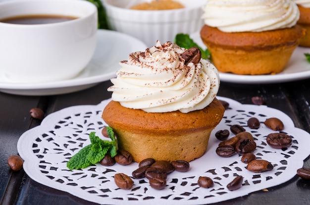 Zoete koffie cupcakes met boterroom en korrels van koffie