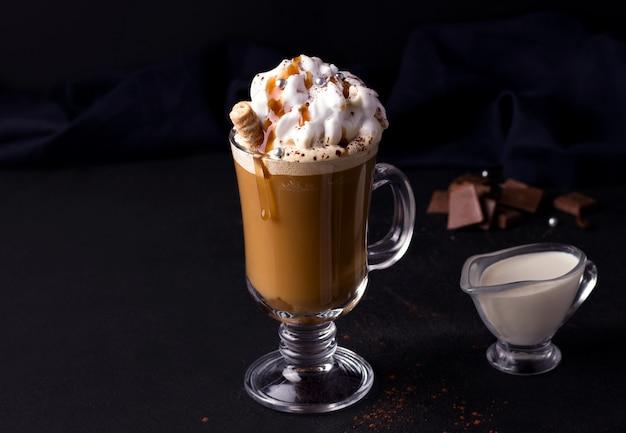 Zoete koffie met karamel en room op een zwarte achtergrond
