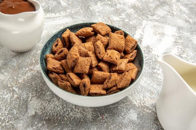 Zoete kussenkoekjes met chocosaus op wit