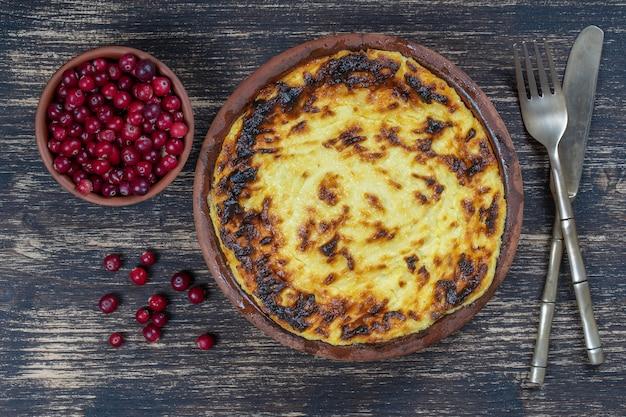 Zoete kwark braadpan met rozijnen en griesmeel op houten tafel. keramische kom met gebakken kwark braadpan, close-up, bovenaanzicht