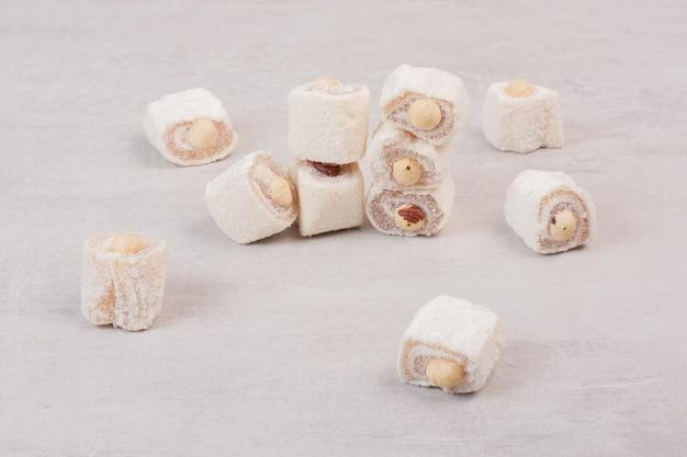 Zoete lekkernijen met noten op witte ondergrond.