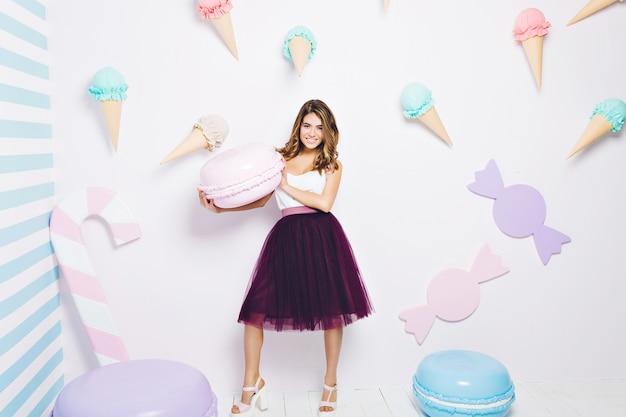 Zoete levensstijl, die positieve emoties uitdrukt van jonge vrouw die in tule rok grote macaron rond snoep houdt. snoep, ijs, geluk, pastelkleuren.