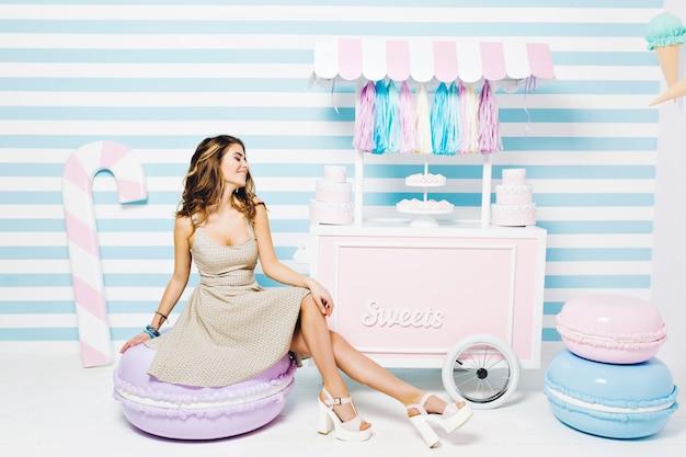 Zoete levensstijl, vrolijke sfeer van vrolijke mooie jonge vrouw in jurk zittend op grote macaron onder snoepjes op gestreepte muur. taarten, snoep, genieten, lachend met gesloten ogen.