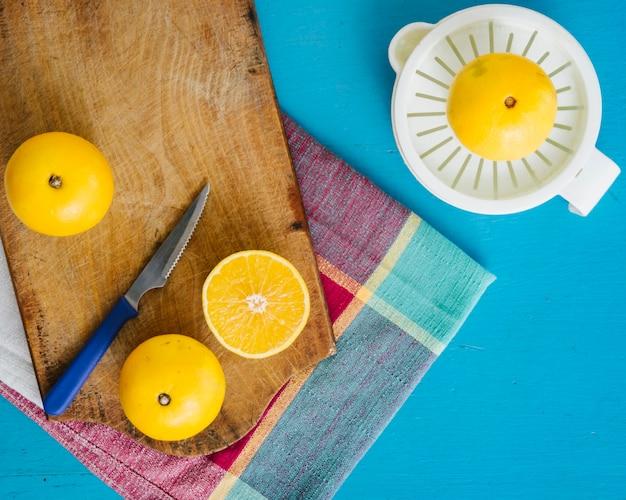 Zoete limoenen en handmatige juicer op blauwe achtergrond