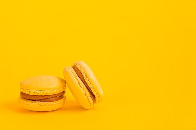Zoete macarondessertcake die op trendy geel wordt geïsoleerd