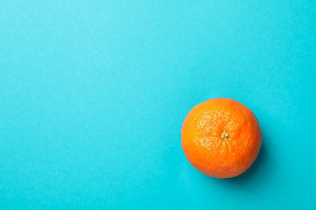 Zoete mandarijn op turquoise achtergrond, ruimte voor tekst
