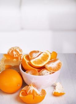 Zoete mandarijnen en sinaasappelen op tafel in kom op kamer