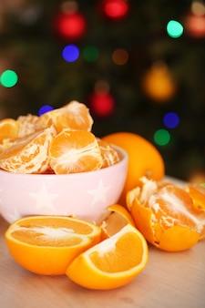 Zoete mandarijnen en sinaasappelen op tafel op de achtergrond van de kerstboom