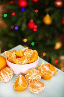 Zoete mandarijnen en sinaasappelen op tafel op het oppervlak van de kerstboom