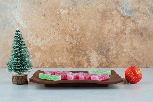 Zoete marmelade met kerstbal en boom op donkere plaat.