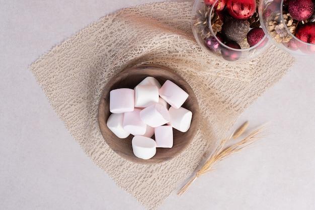 Zoete marshmallows op een houten bord op jute