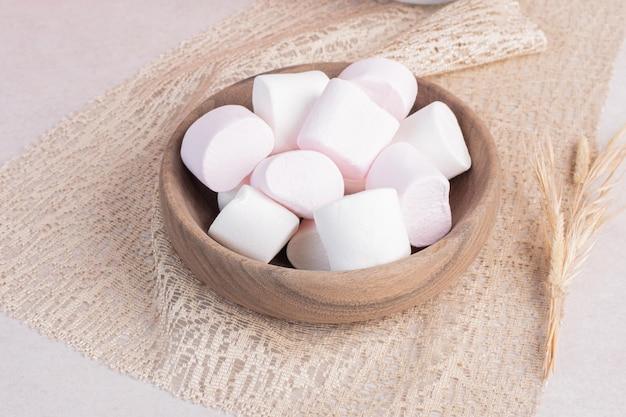 Zoete marshmallows op houten bord op jute