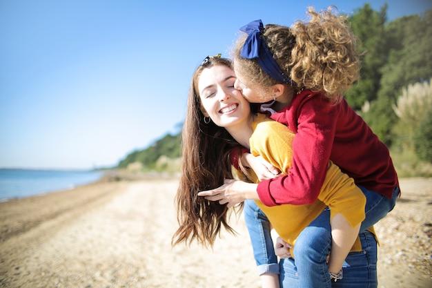 Zoete moeder die haar dochter op haar rug vervoert die wit bij het strand loopt