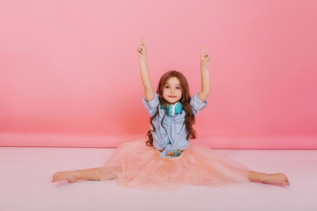 Zoete momenten gelukkige jeugd van geweldig jong meisje in tule rok qymnastics splitsen op witte vloer op roze achtergrond. leuk modieus kind met lang donkerbruin haar, blauwe headhones op de nek