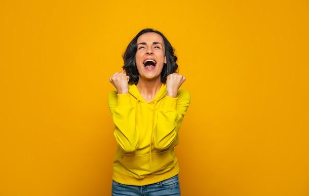 Zoete overwinning. schreeuwend meisje gekleed in een gele hoodie, triomf vieren met gebalde vuisten en blije ogen omhoog geheven.