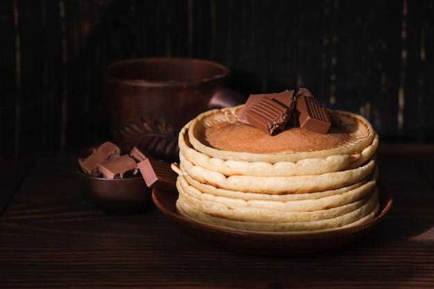 Zoete pannenkoeken chocolade topping. zelfgemaakte pannenkoeken met chocoladeontbijt. ochtend dessert cacaopannenkoekjes op een plaat