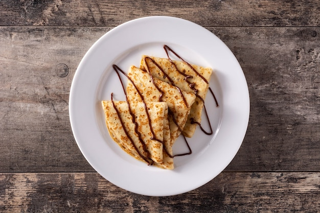 Zoete pannenkoeken met chocolade op houten tafel
