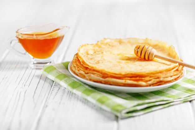 Zoete pannenkoeken met honing op de tafel
