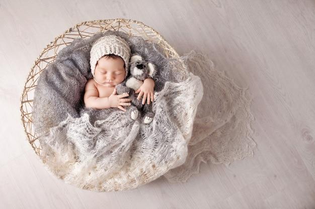 Zoete pasgeboren baby slaapt in een mand. mooie pasgeboren jongen met berenstuk speelgoed. kopieer ruimte