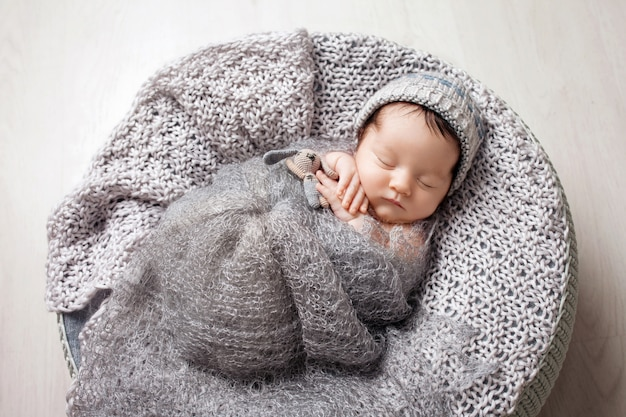 Zoete pasgeboren baby slaapt in een mand.