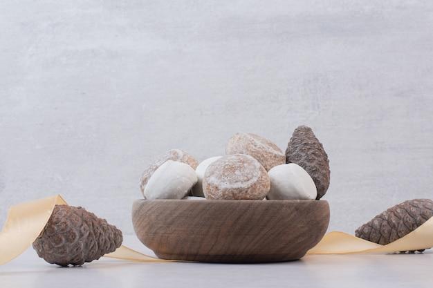Zoete peperkoek met dennenappel op houten plaat.