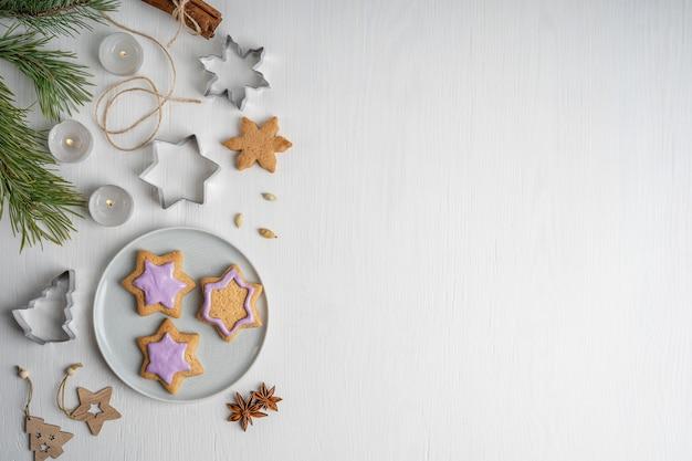Zoete peperkoekkoekjes met violet suikerglazuur dat op grijze plaat op witte houten lijst met kaarsen wordt gediend