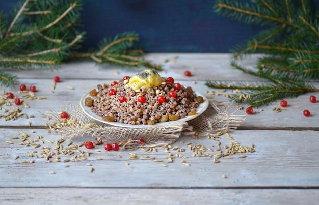 Zoete pilaf met gedroogd fruit. moderne kutia met gekonfijt fruit. bord met kutia met gedroogd fruit. kerstpap met rozijnen, gekonfijte sinaasappel en amandelen.