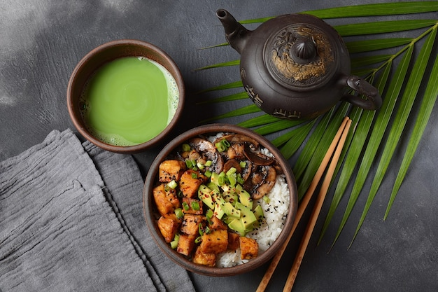 Zoete, pittige, knapperige en gebakken tofu in teriyakisaus geserveerd in een kom met rijst.