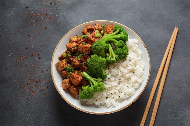 Zoete, pittige, krokante en gebakken tofu in teriyakisaus geserveerd met rijst.