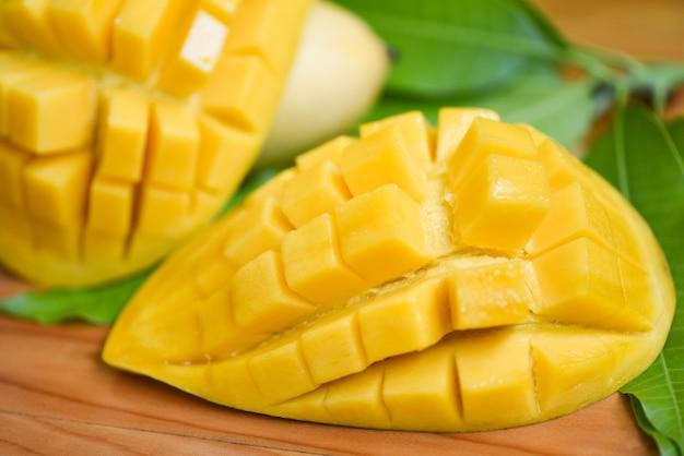 Zoete rijpe gesneden mango's - mangoplak en mangobladeren van het fruitconcept van de boom tropisch zomer